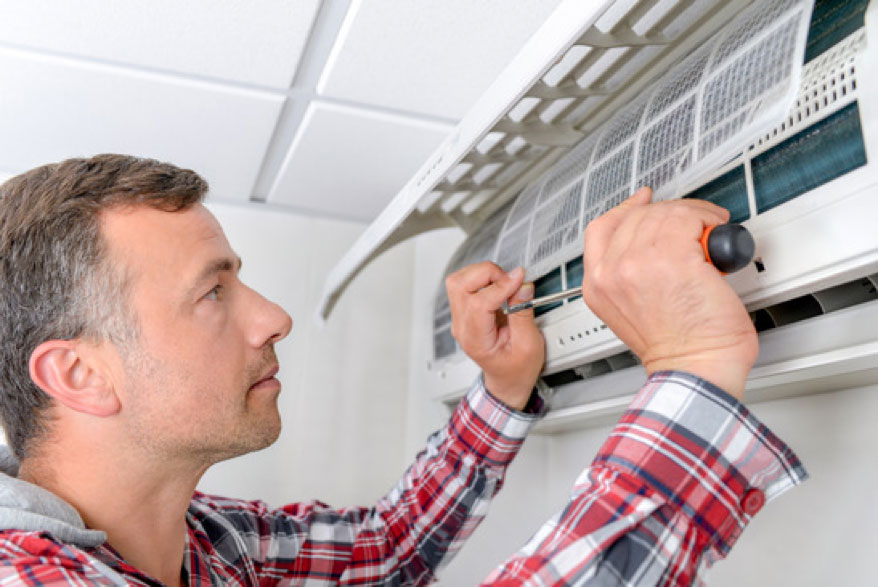 Man Fixing Air Conditioner - Entek HVAC